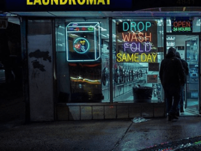 A night shot of the neon signs in front of a laundry mat.