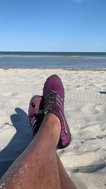 2 crossed feet with water shoes on at the beach.