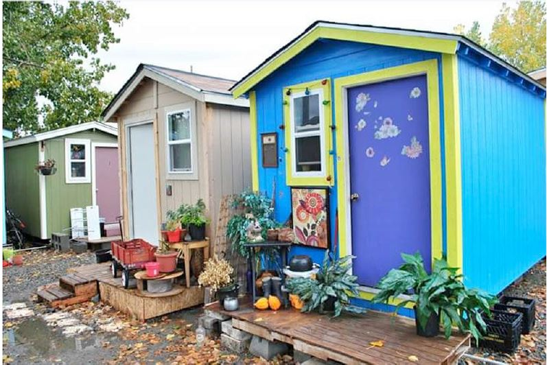 3 colorful tiny homes next to each other in a row.